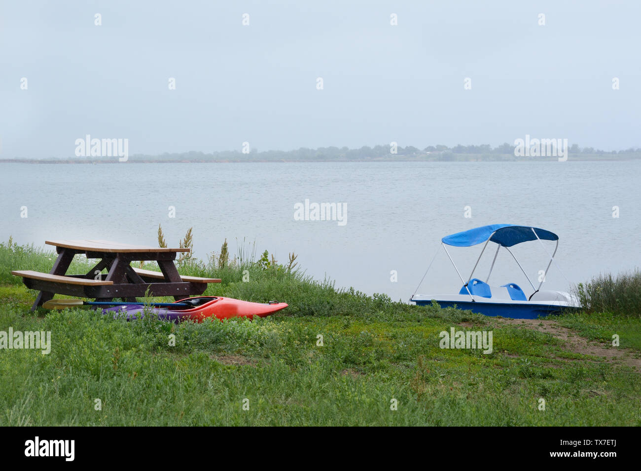 Kayak and boat grounded on grassy lake shore near picnic table during rain storm at lake - Stock Image
