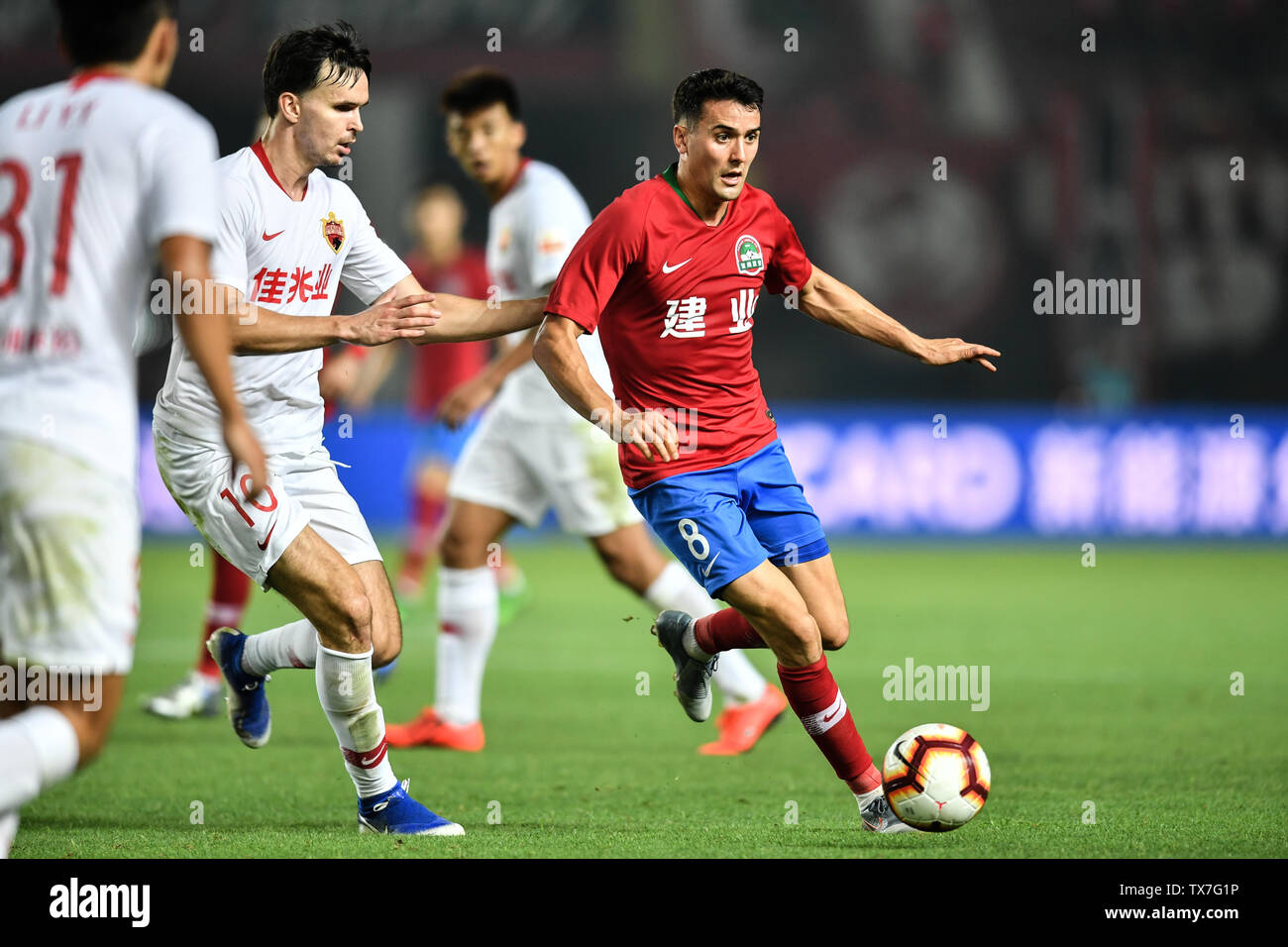 English-born Taiwanese football player Tim Chow, right, of Henan Jianye passes the ball against Norwegian football player Ole Selnaes of Shenzhen F.C. in their 14th round match during the 2019 Chinese Football Association Super League (CSL) in Zhengzhou city, central China's Henan province, 22 June 2019. Henan Jianye defeated Shenzhen F.C. 1-0. Stock Photo