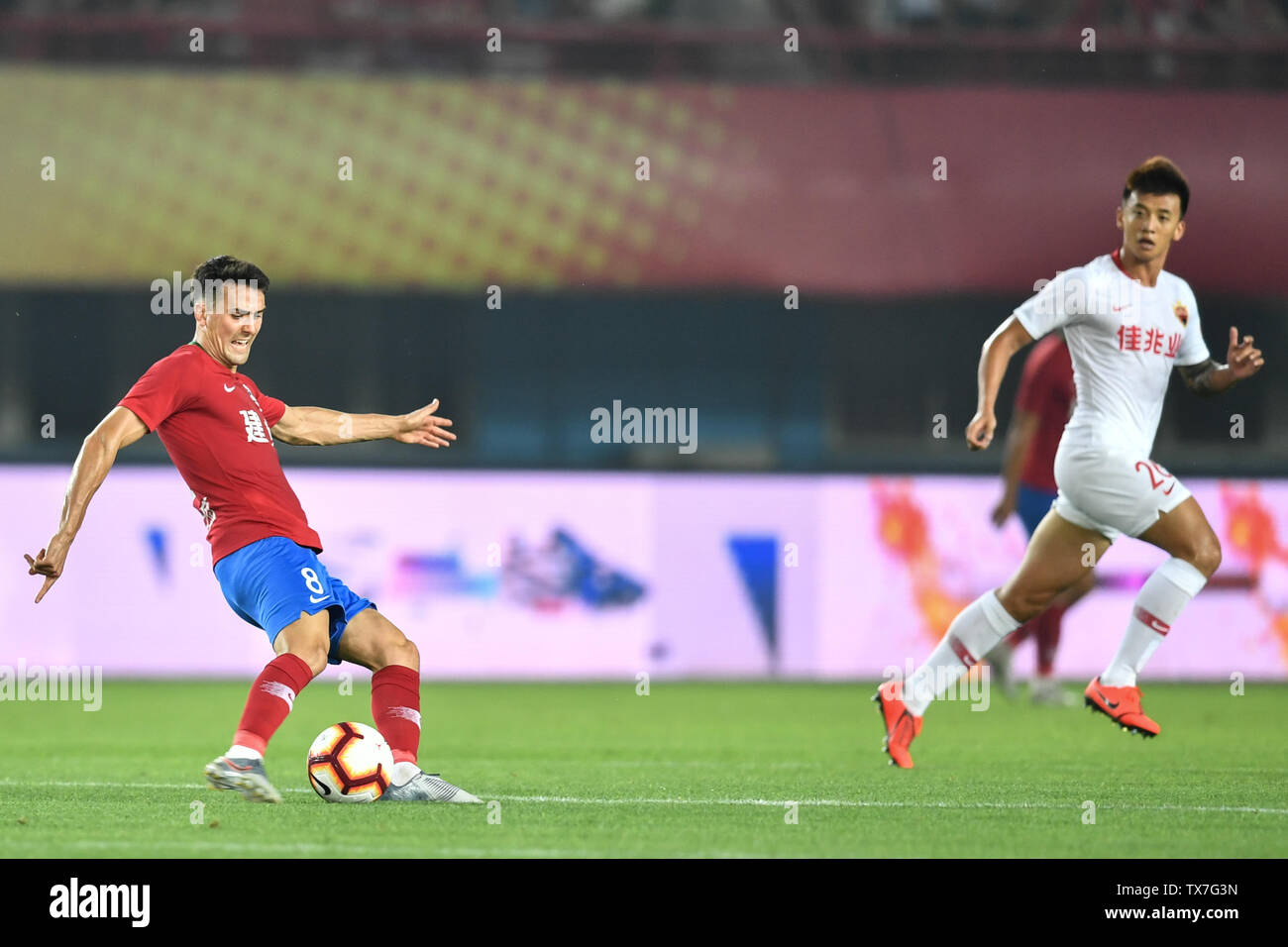 English-born Taiwanese football player Tim Chow, left, of Henan Jianye passes the ball against a player of Shenzhen F.C. in their 14th round match during the 2019 Chinese Football Association Super League (CSL) in Zhengzhou city, central China's Henan province, 22 June 2019. Henan Jianye defeated Shenzhen F.C. 1-0. Stock Photo