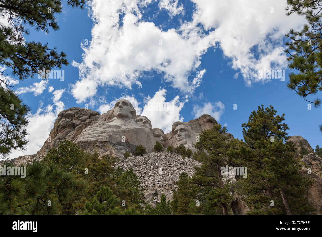 Blue sky and white fluffy clouds provide a striking back drop for the carved faces of four famous United States Presidents in Mount Rushmore National - Stock Image