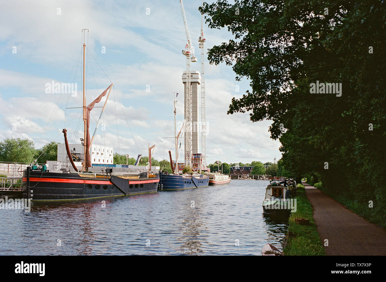 The River Lea Navigation at Tottenham Hale, London UK,  with moored river boats and the new Hale Wharf development under construction - Stock Image