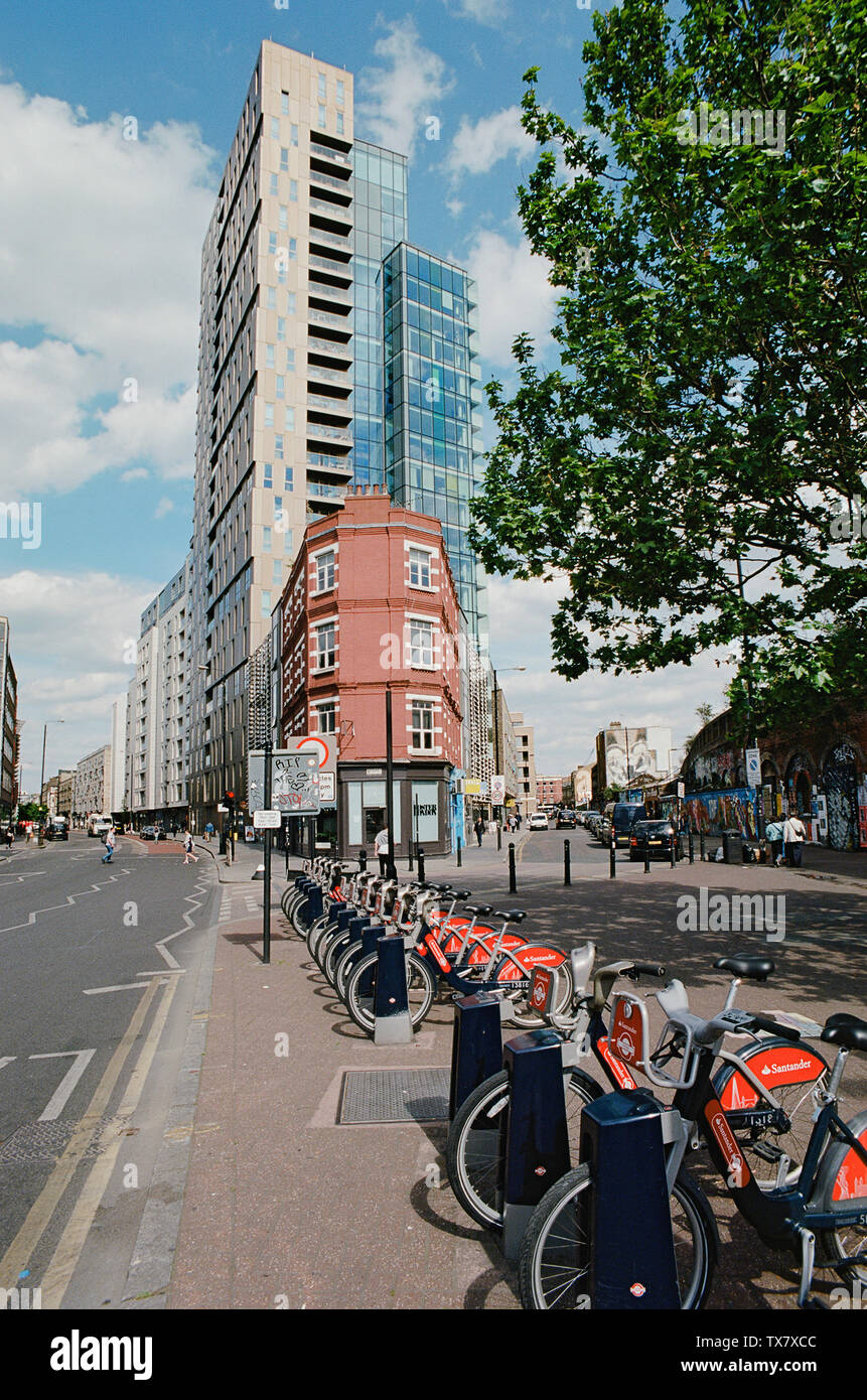 Bethnal Green Road at the junction with Sclater Street, in London's East End, with new apartment buildings - Stock Image