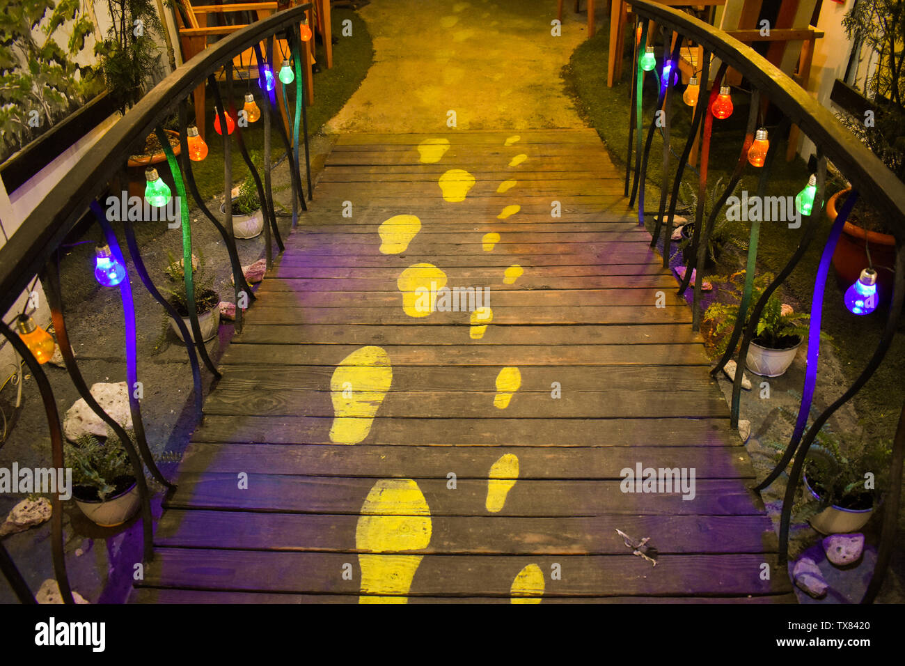 Innovative idea of human foot traces on the wooden pathway with colorful lights hanging on the railings.  Attractive hidden gem travel destination in - Stock Image