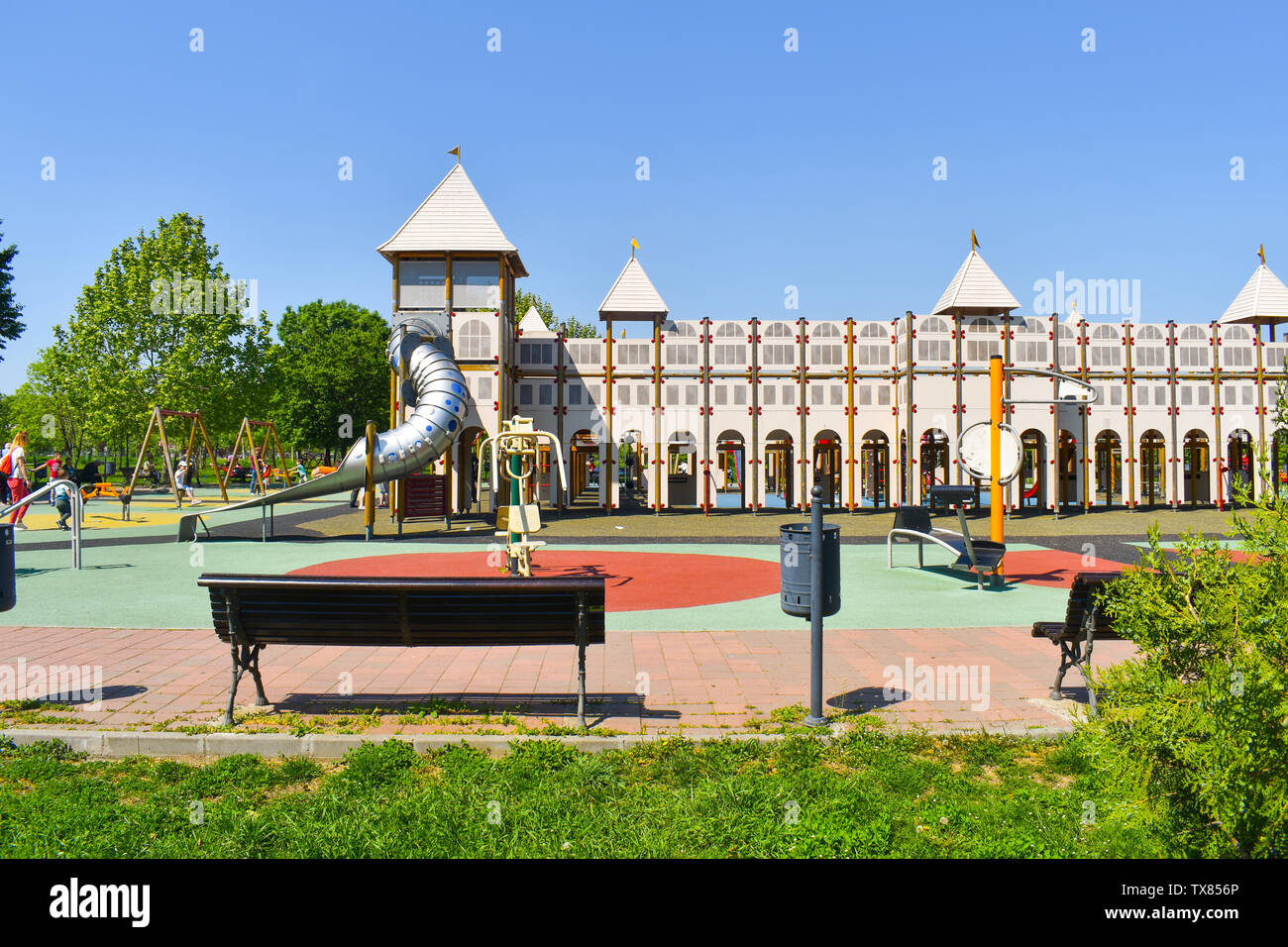 Castle playground for kids in the central park of the city. Beautiful palace playground idea for playing kids with their families. Colorful slides, sw - Stock Image