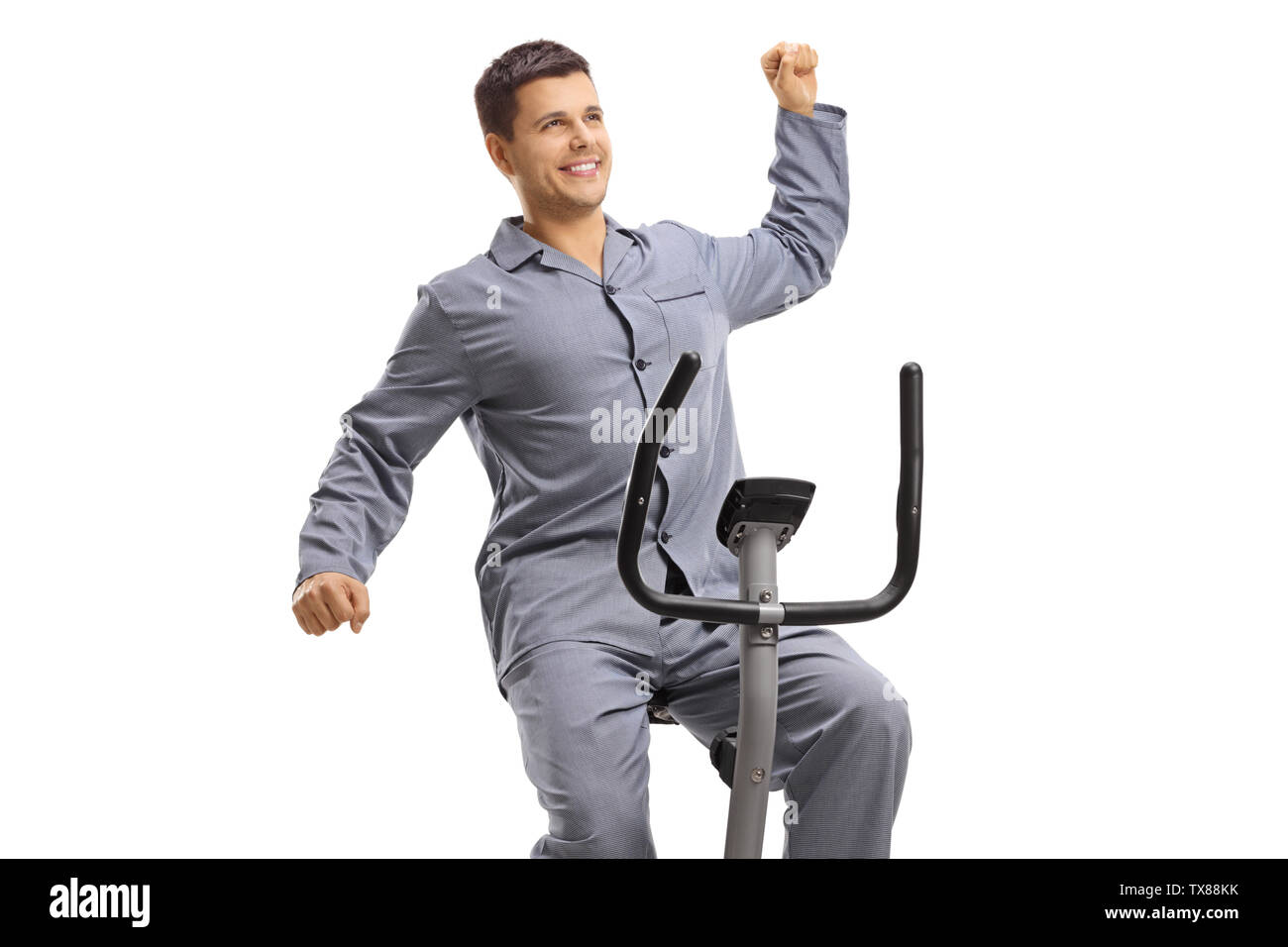 Young guy in pajams stretching on an exercise bike isolated on white background - Stock Image
