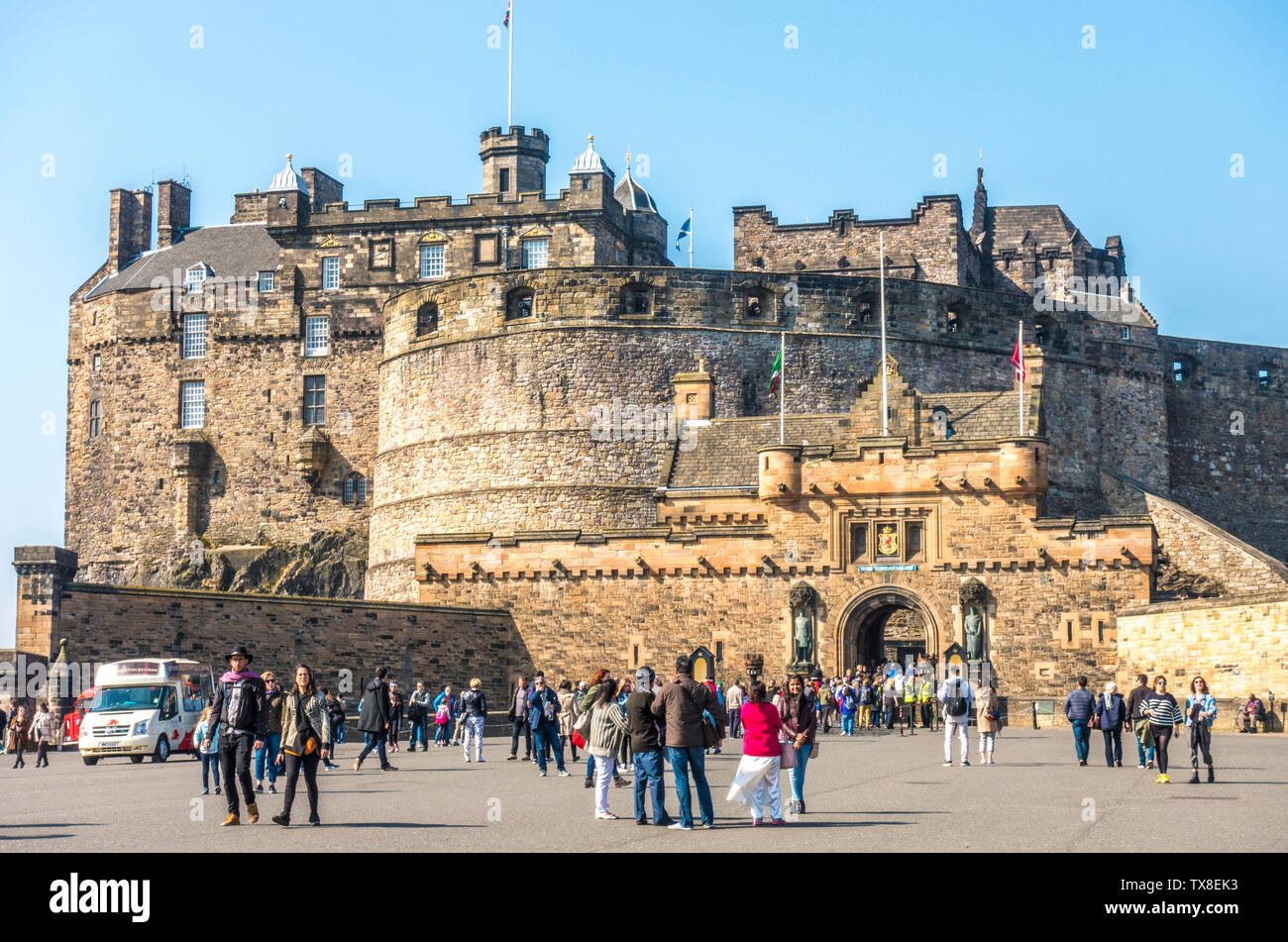 Wide view of visitors on the esplanade, with others going in an out of the main front entrance to Edinburgh Castle, Scotland, UK. Stock Photo