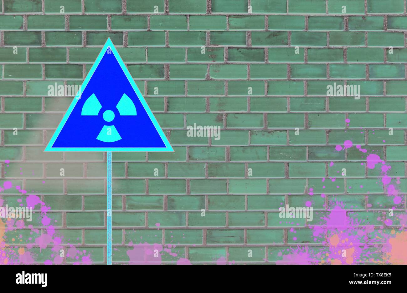 Yellow triangle sign with an international Radioactive Symbol on messy and dirty brick wall background. Digital mock-up. - Stock Photo