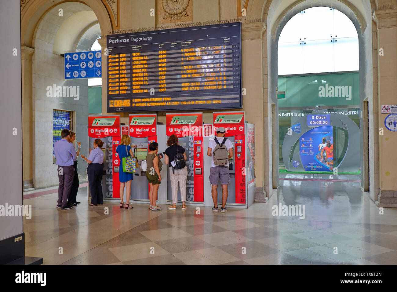 Customers purchasing train tickets from automated machine below the train departure board.  Trieste, Italy, June 17, 2019 Stock Photo