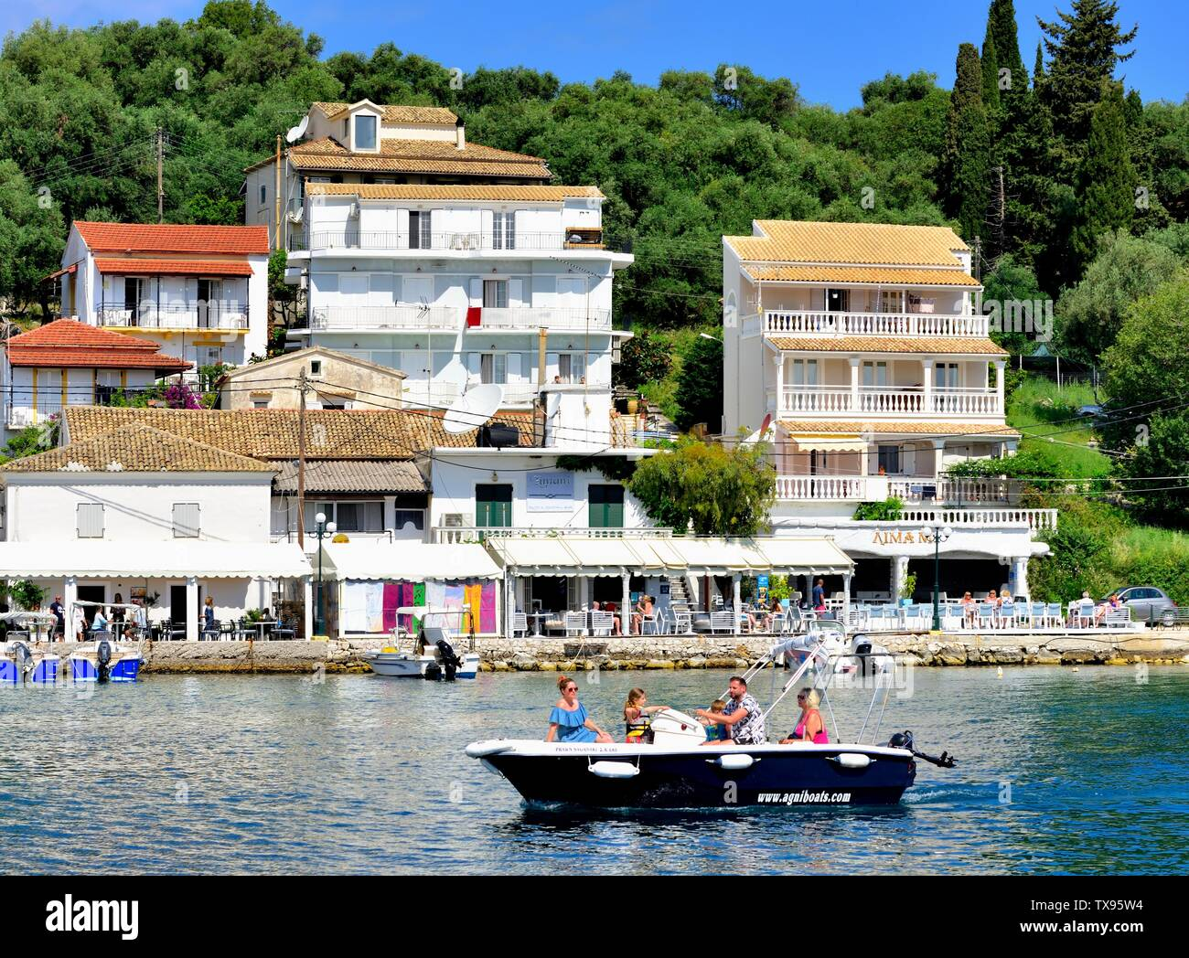 Tourists arriving at Kassiopi bay in a hire boat,Kassopaia,Ionian Islands, Corfu ,Greece Stock Photo