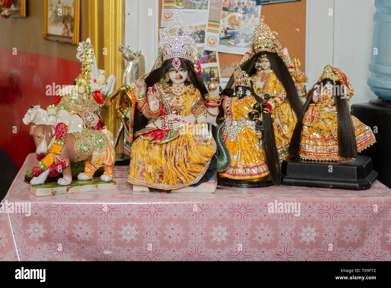 Small statues of Hindu deities with new clothing that was handmade as part of a ritual of giving thanks. In Queens, New York City. - Stock Image