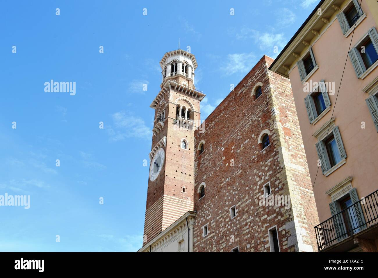 Close-up view to the dei Lamberti medieval tower with clock of the Palace della Ragione in Verona. Stock Photo
