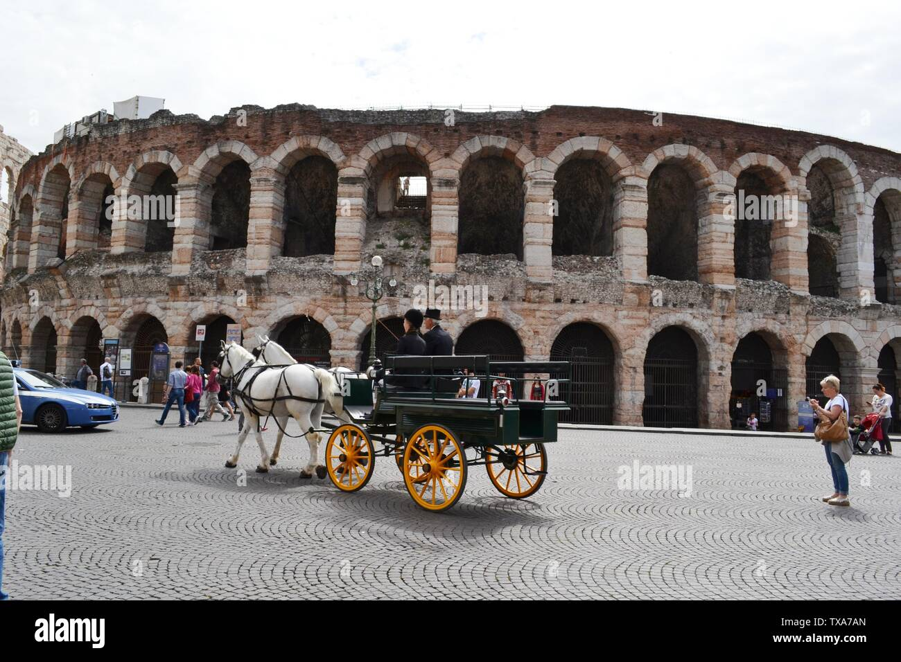 Verona/Italy - May 9, 2015: Two horses carriage moving in Piazza Bra along Arena di Verona, the famous summer open stage theater. Stock Photo