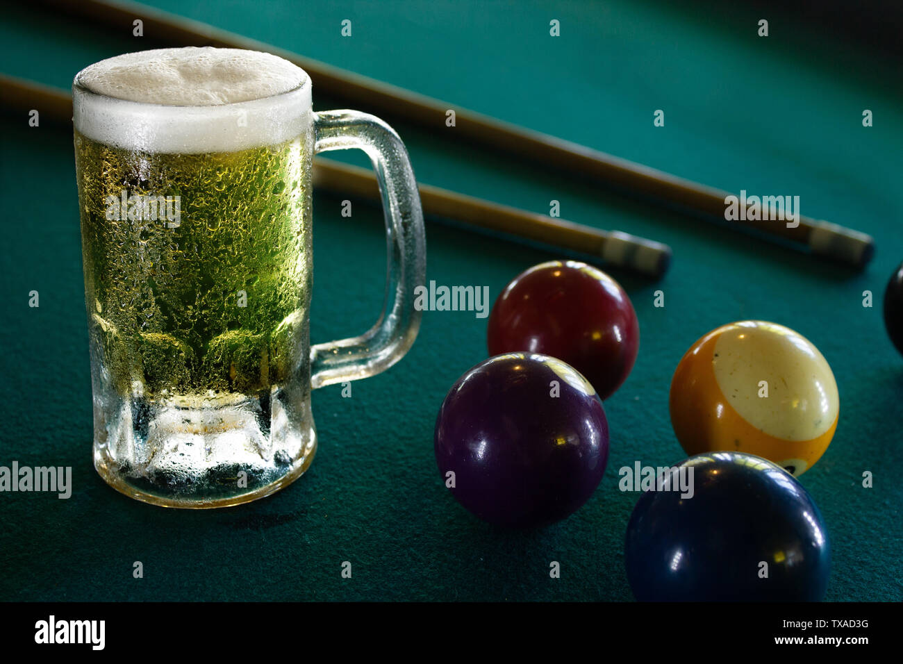 a frozen beer mug on a green billiard table, frozen, cold beer - Stock Image