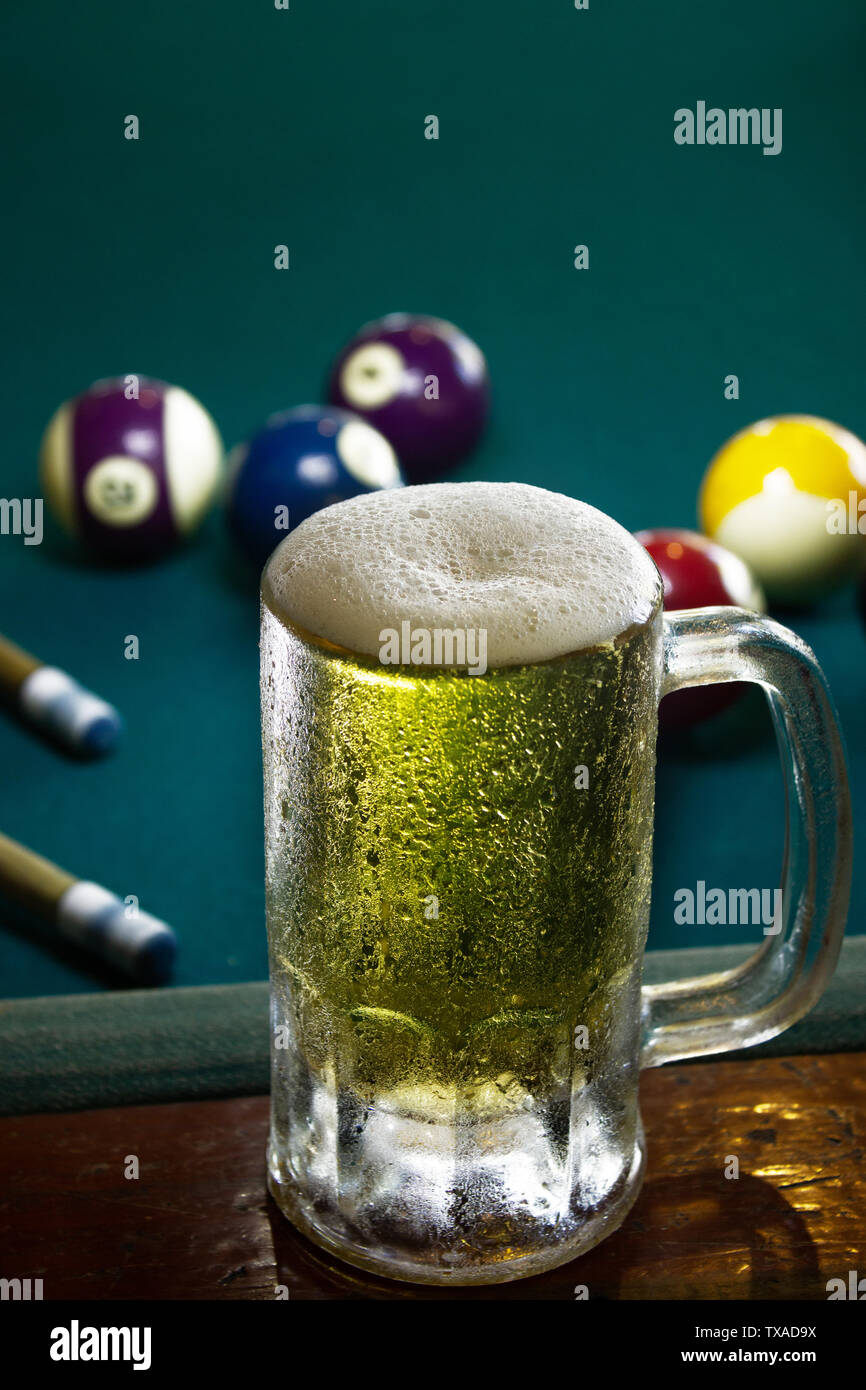 a frozen beer mug with foam on a green billiard table, frozen, cold beer - Stock Image