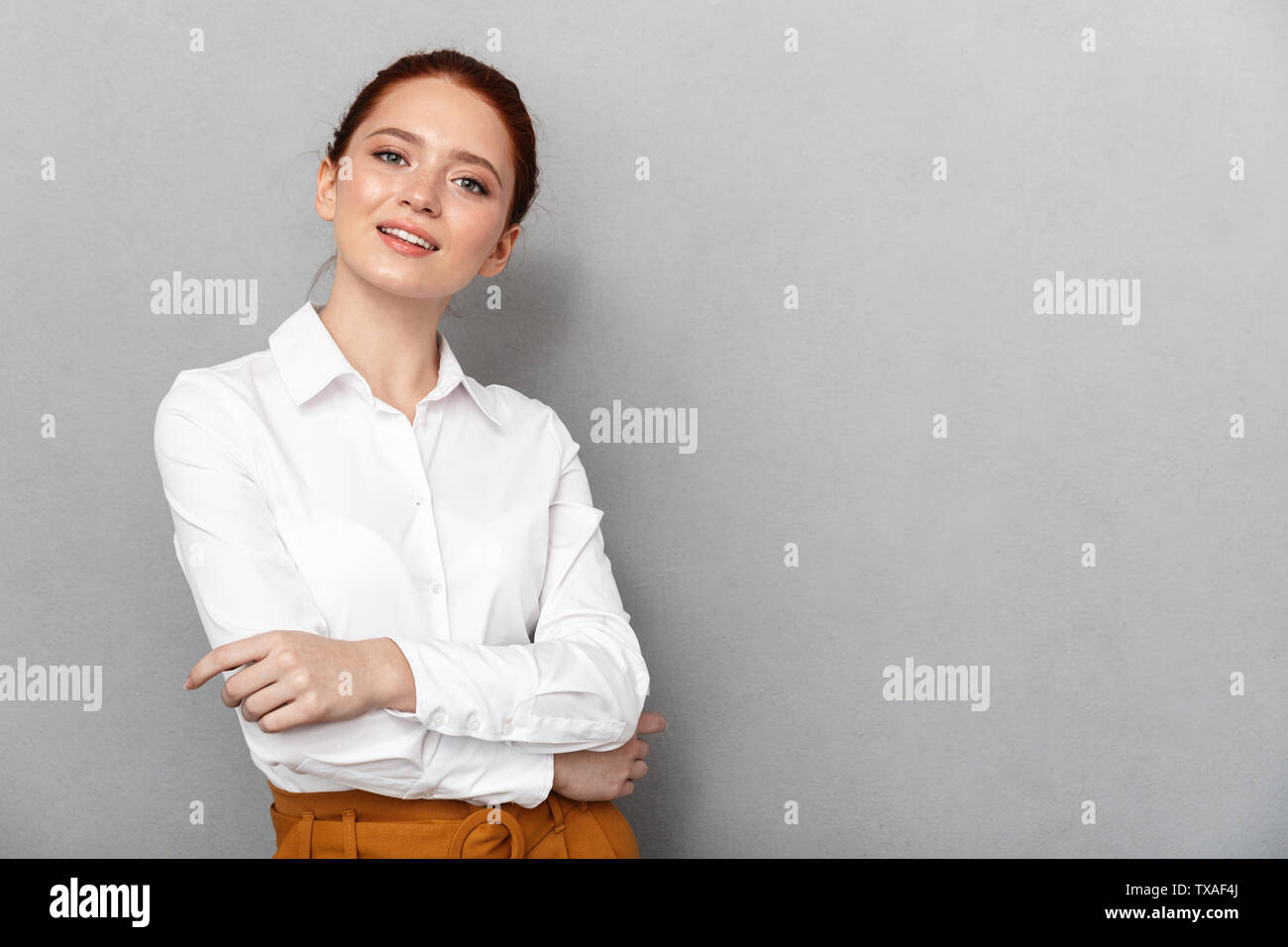Portrait of caucasian redhead businesswoman 20s in formal wear smiling at camera and posing in office isolated over gray background - Stock Image