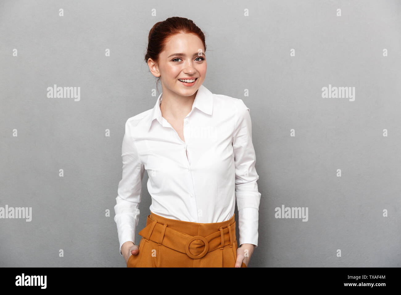 Portrait of cheerful redhead businesswoman 20s in formal wear smiling at camera and posing in office isolated over gray background - Stock Image