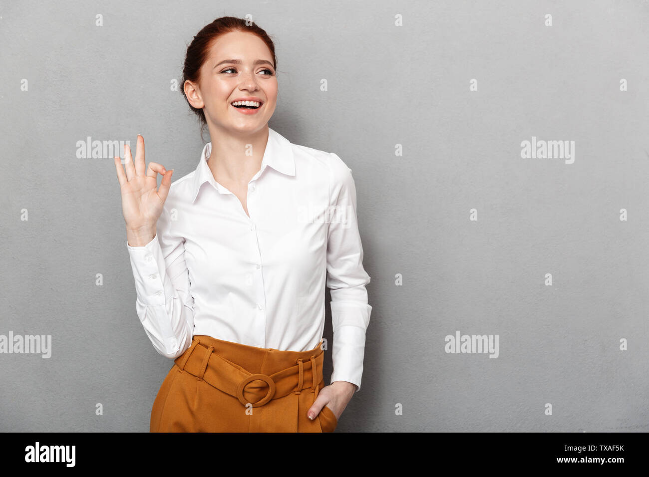 Portrait of european redhead businesswoman 20s in formal wear smiling at camera and showing ok sign in office isolated over gray background - Stock Image