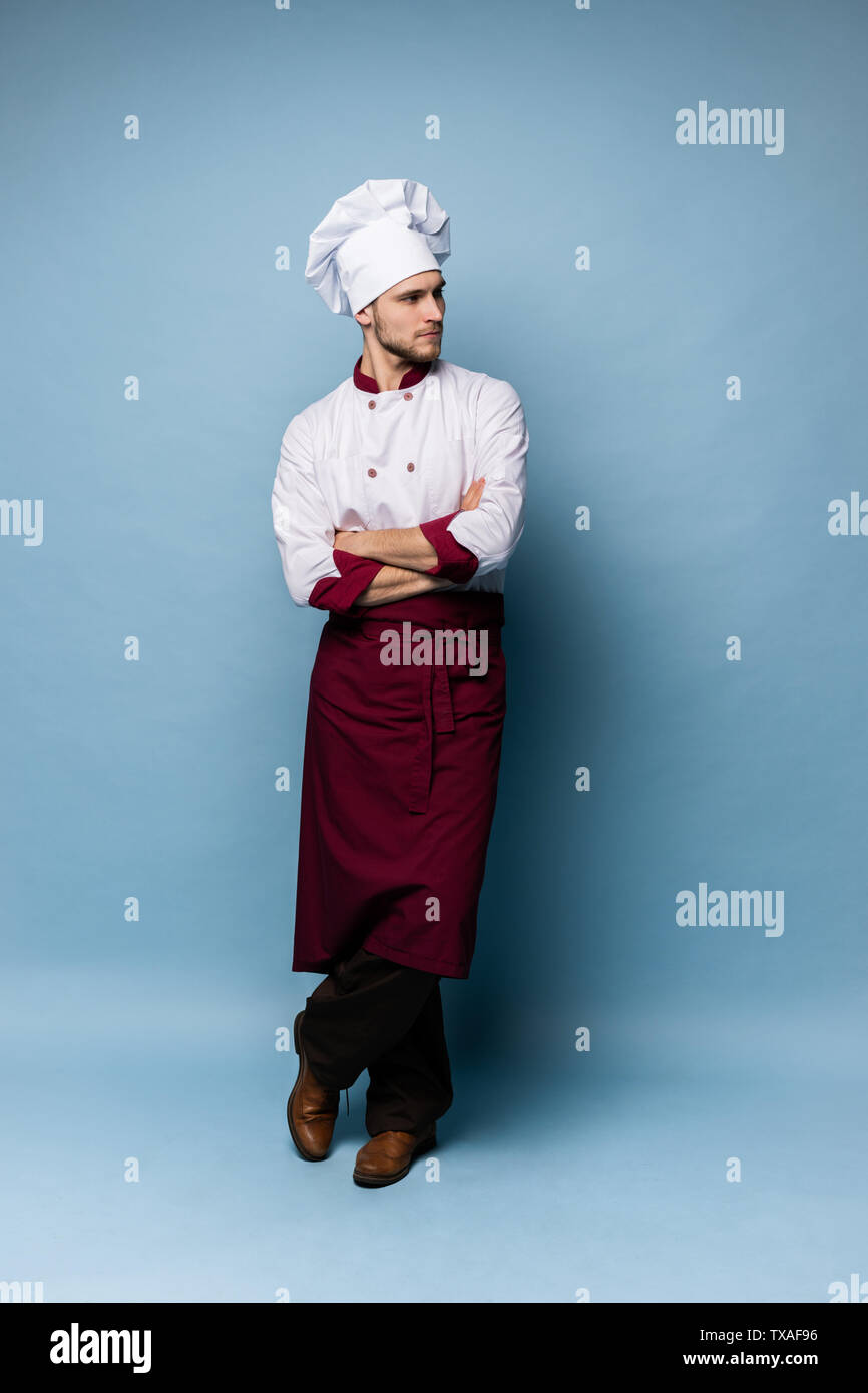 Full length portrait of cheerful joyful chef cook with stubble in beret and white outfit looking at camera isolated - Stock Image