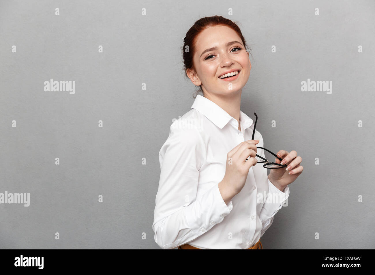 Portrait of caucasian redhead businesswoman 20s in formal wear holding eyeglasses and smiling at camera in office isolated over gray background - Stock Image