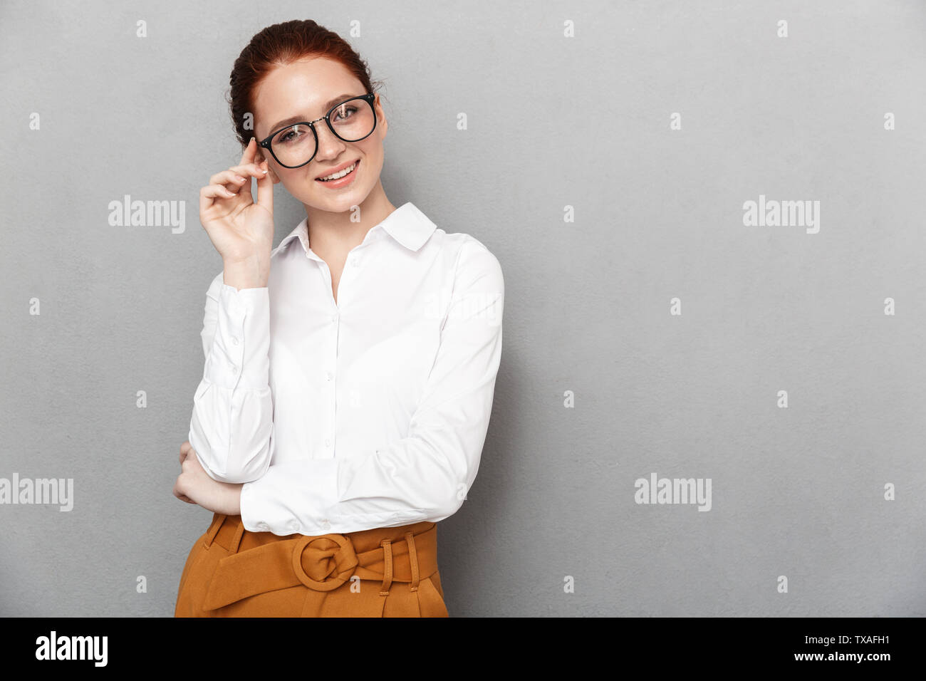 Portrait of happy redhead businesswoman 20s in formal wear holding eyeglasses and smiling at camera in office isolated over gray background - Stock Image
