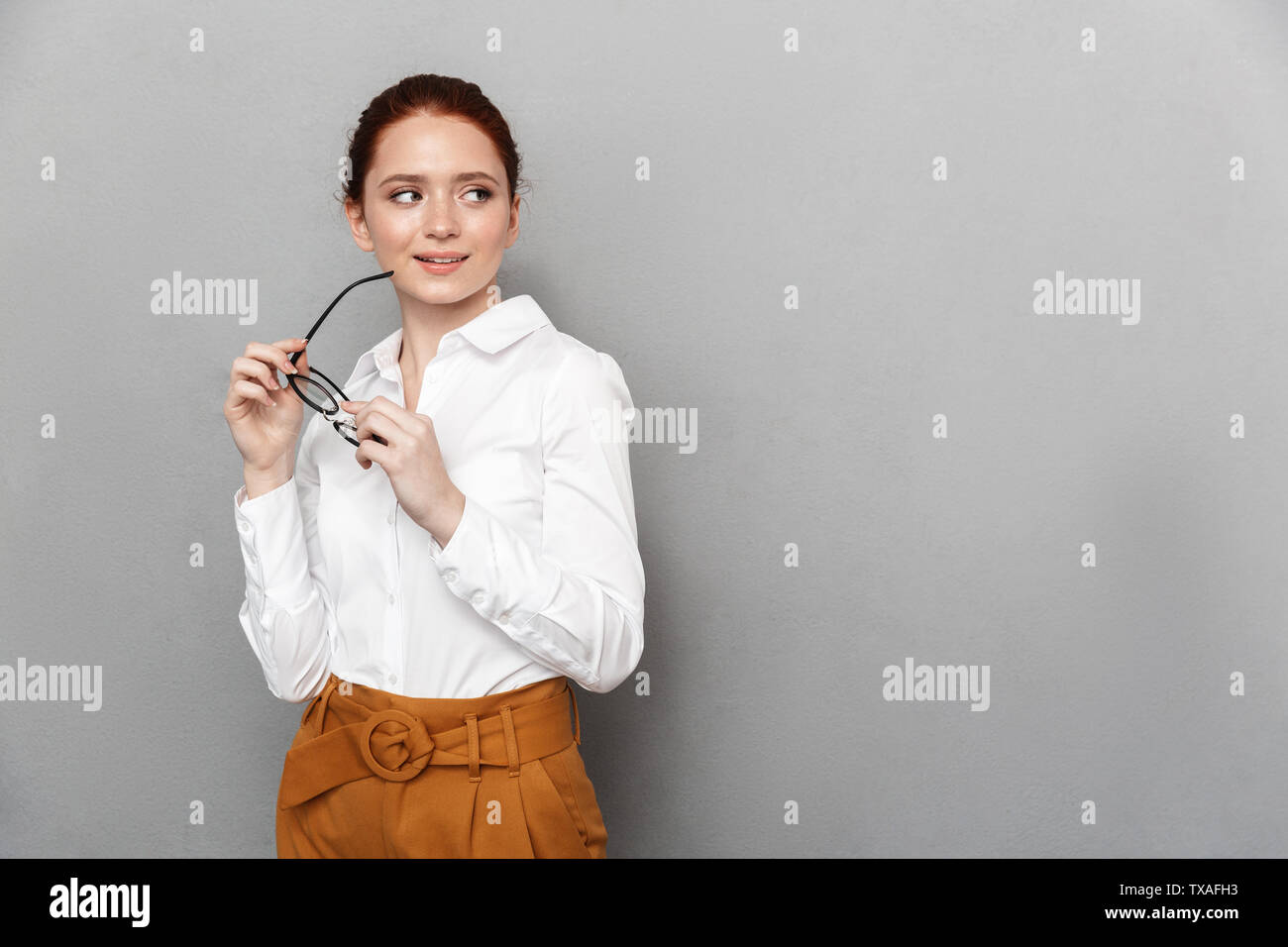 Portrait of successful redhead businesswoman 20s in formal wear holding eyeglasses and smiling at camera in office isolated over gray background - Stock Image