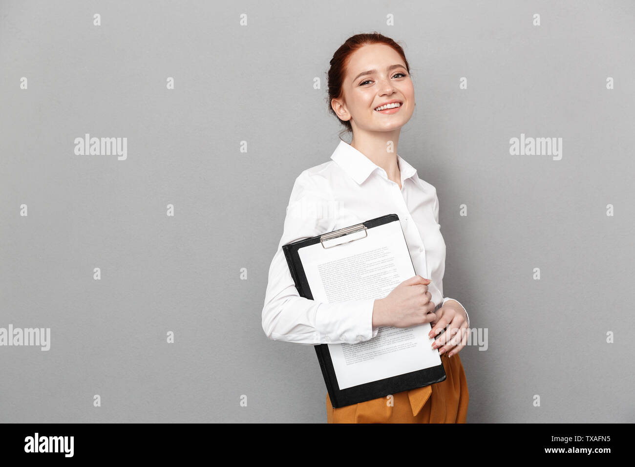 Portrait of content redhead businesswoman 20s dressed in formal wear holding clipboard with documents and smiling at camera in office isolated over gr - Stock Image