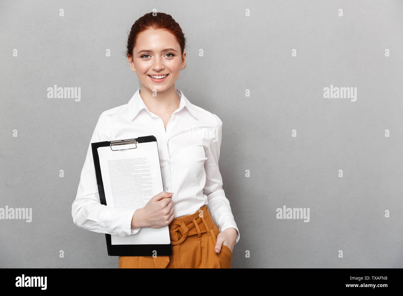 Portrait of cute redhead businesswoman 20s dressed in formal wear holding clipboard with documents and smiling at camera in office isolated over gray - Stock Image