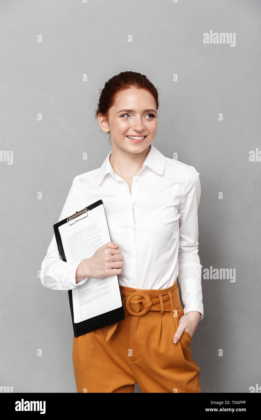 Portrait of successful redhead businesswoman 20s dressed in formal wear holding clipboard with documents and smiling at camera in office isolated over - Stock Image