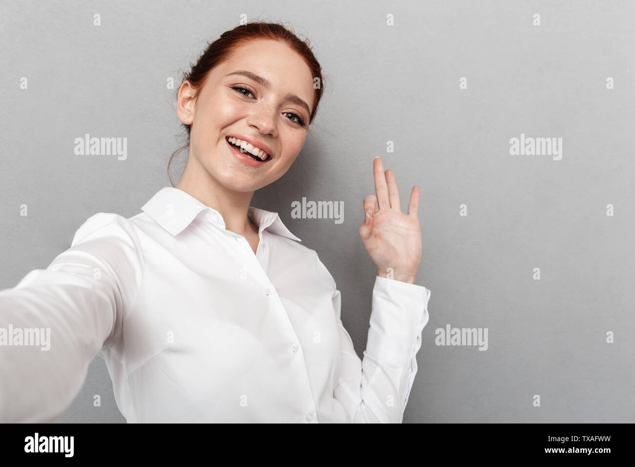 Image of caucasian redhead businesswoman 20s in formal wear smiling at camera while taking selfie photo isolated over gray background - Stock Image