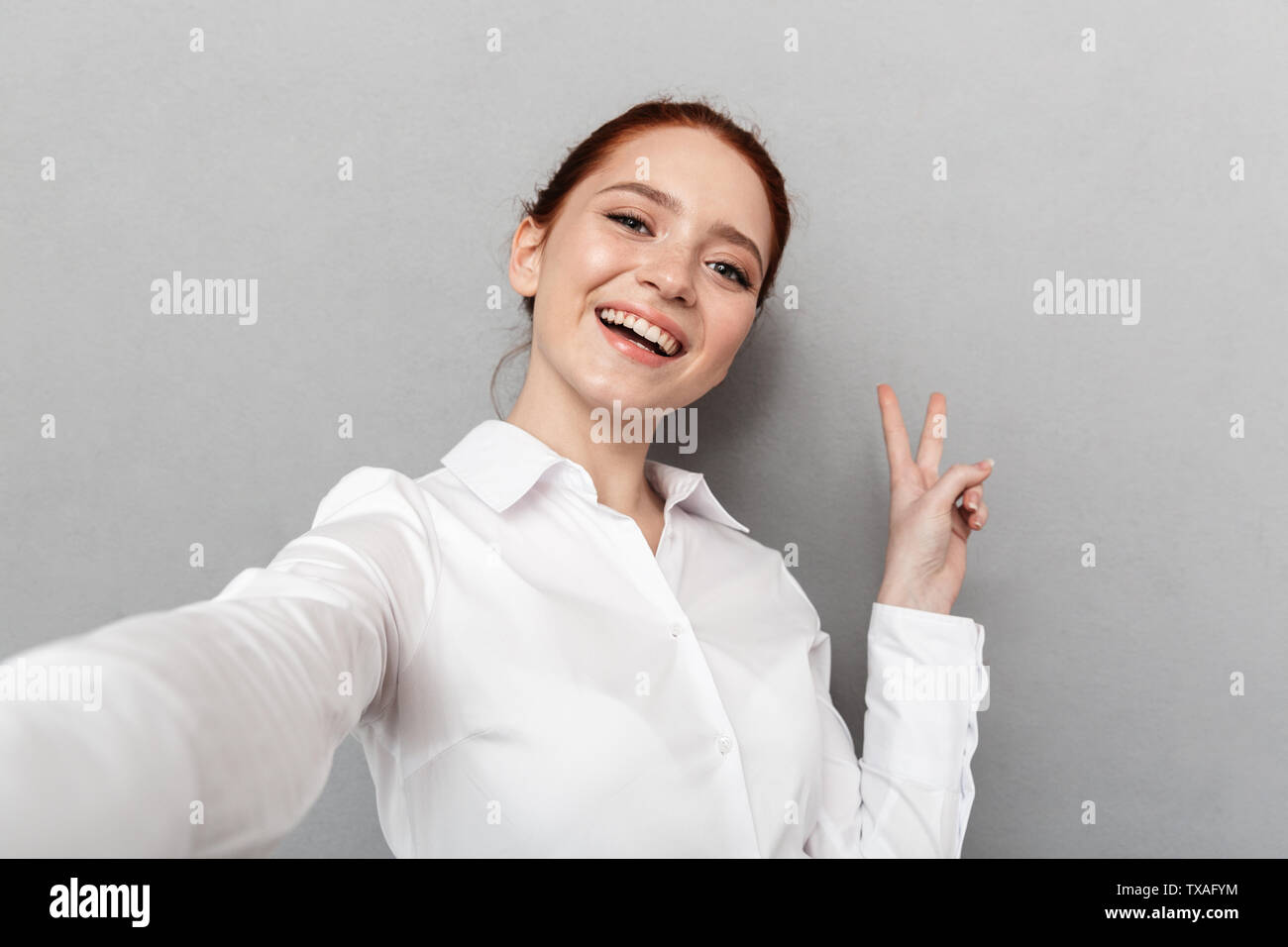 Image of successful redhead businesswoman 20s in formal wear smiling at camera while taking selfie photo isolated over gray background - Stock Image