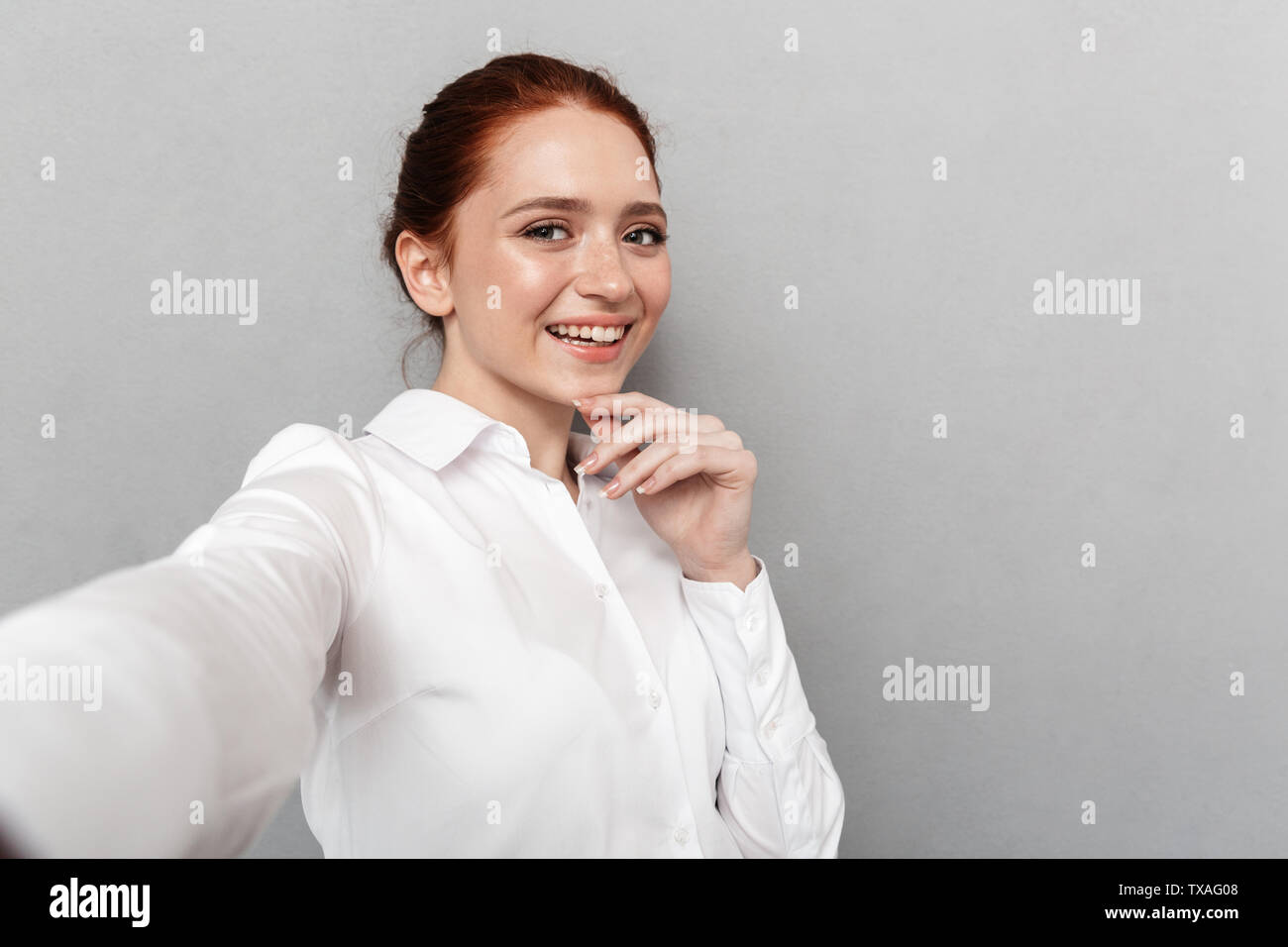 Image of young redhead businesswoman 20s in formal wear smiling at camera while taking selfie photo isolated over gray background - Stock Image