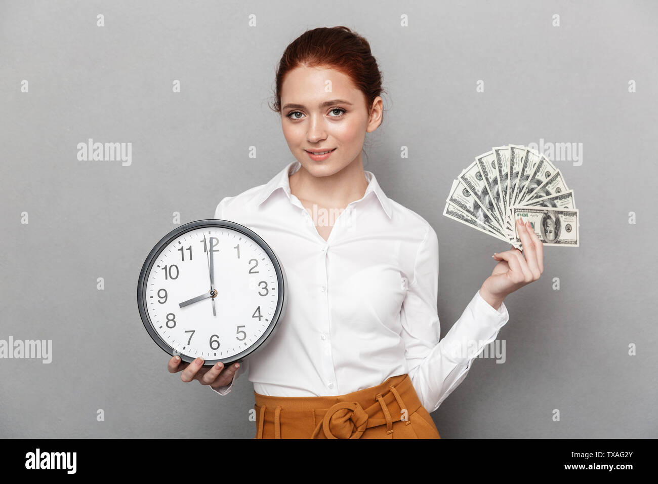 Image of pretty redhead businesswoman 20s in formal wear holding big clock and bunch of money cash isolated over gray background - Stock Image