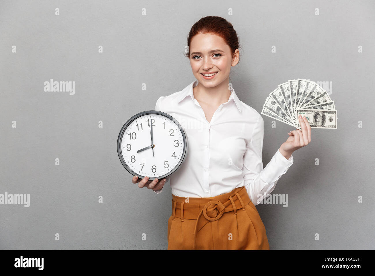 Image of european redhead businesswoman 20s in formal wear holding big clock and bunch of money cash isolated over gray background - Stock Image