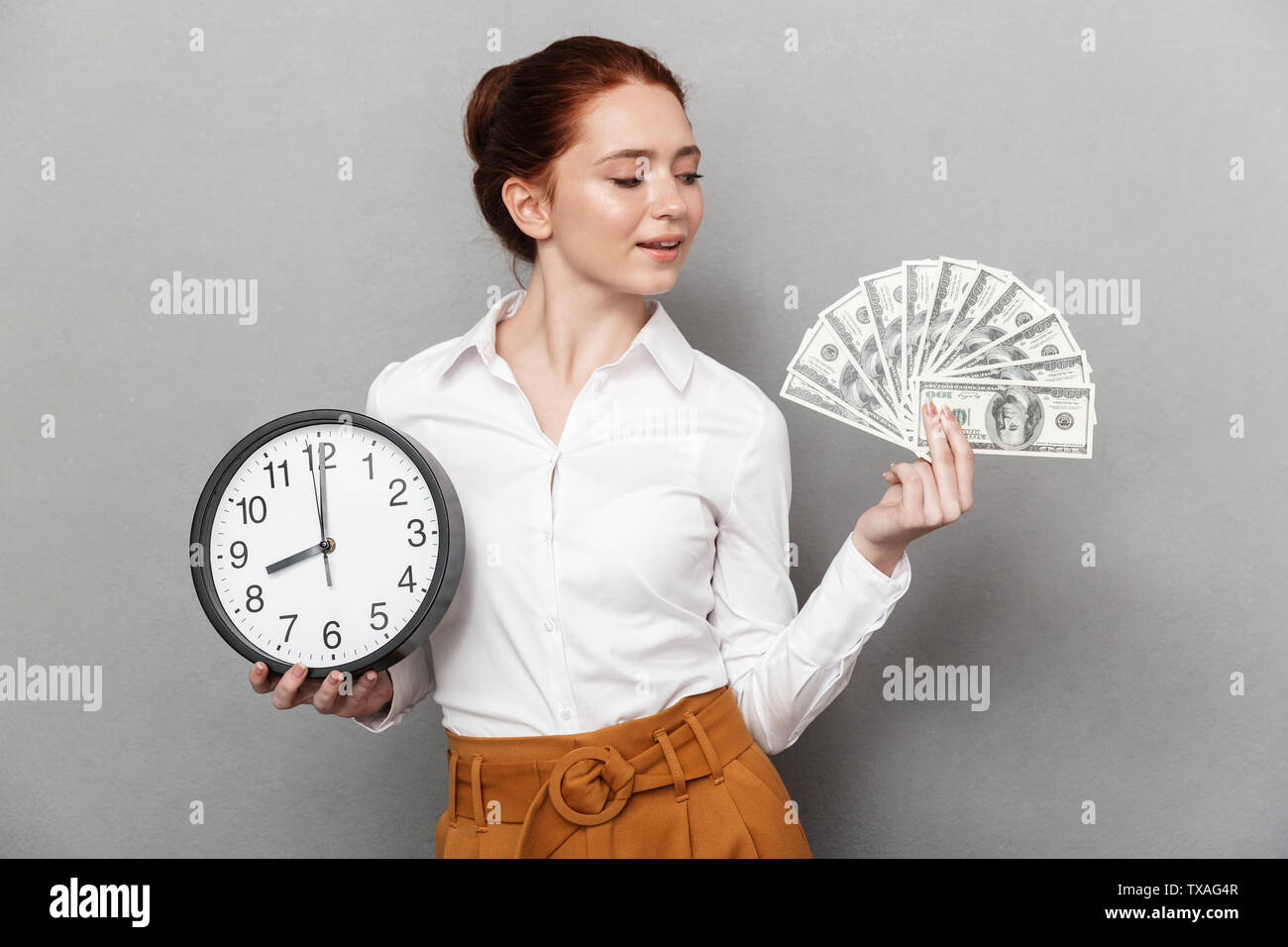 Image of charming redhead businesswoman 20s in formal wear holding big clock and bunch of money cash isolated over gray background - Stock Image