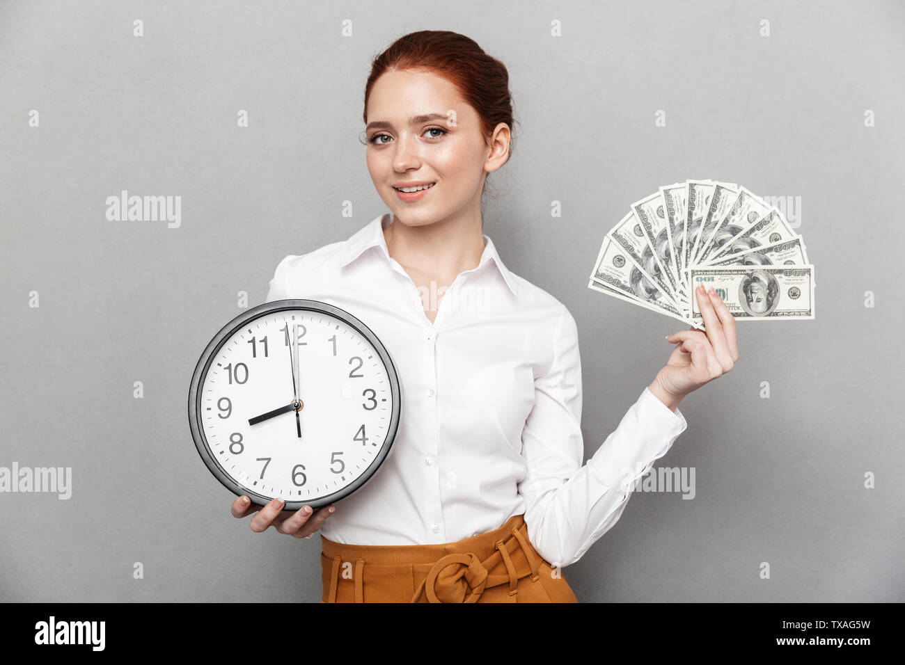 Image of cheerful redhead businesswoman 20s in formal wear holding big clock and bunch of money cash isolated over gray background - Stock Image
