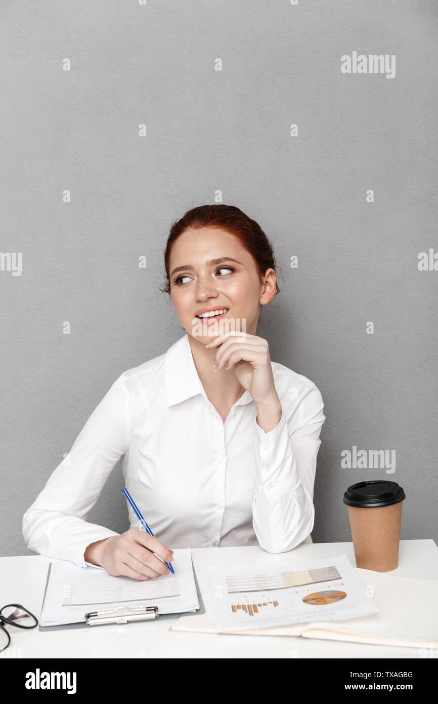 Image of european redhead businesswoman 20s in formal wear writing down notes while working in office isolated over gray background - Stock Image