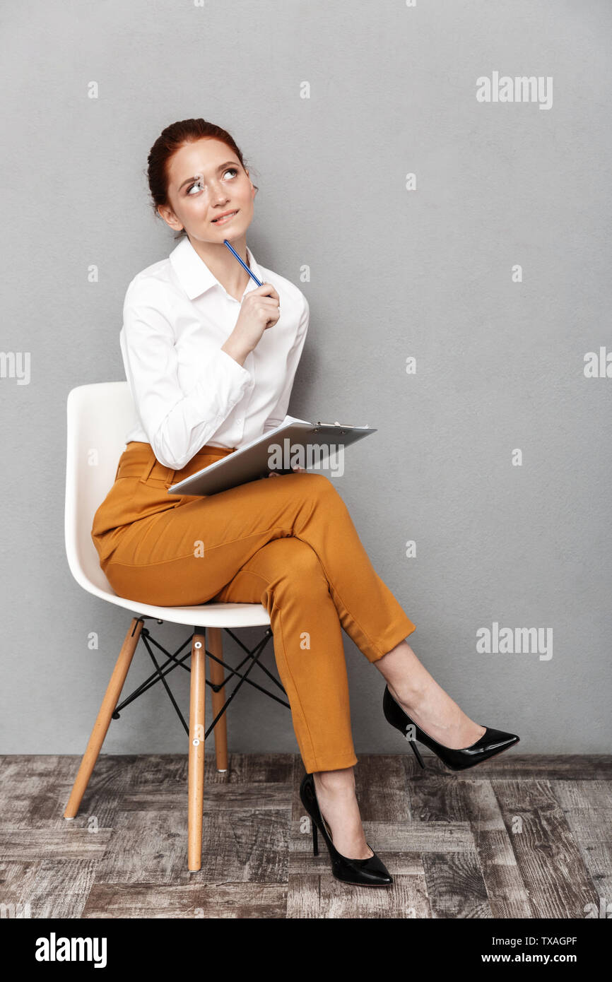 Image of pleased redhead businesswoman 20s in formal wear holding clipboard while sitting on chair in office isolated over gray background - Stock Image