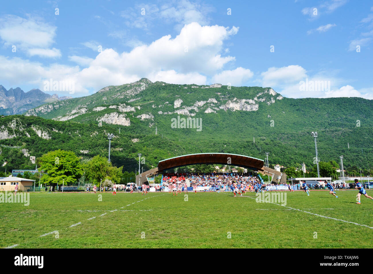 Lecco/Italy - May 24, 2015: Mountain Resegone over Lecco and the rugby match between Rugby Lecco and ASD Rugby Casale on the sports field Lecco Bione. Stock Photo