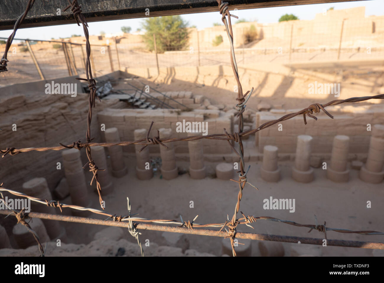 Unclearly depicted columns of an excavated temple near Kerma in Sudan behind sharply focused barbed wire - Stock Image