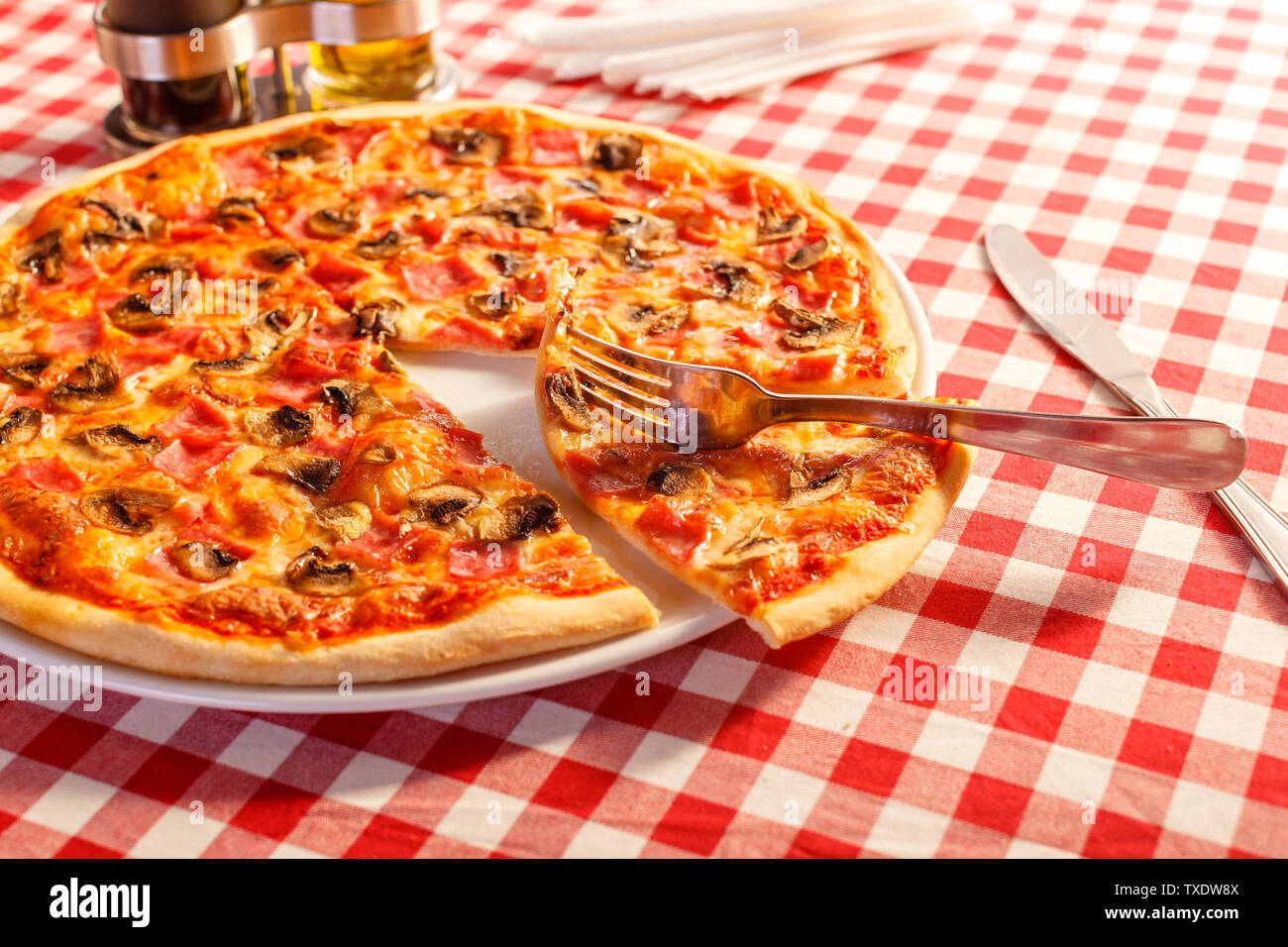 Close up fork takes a piece. Pizza with ham and mushrooms. Delicious hot food sliced and served on white platter. Menu photo, Italian fast food. - Stock Image