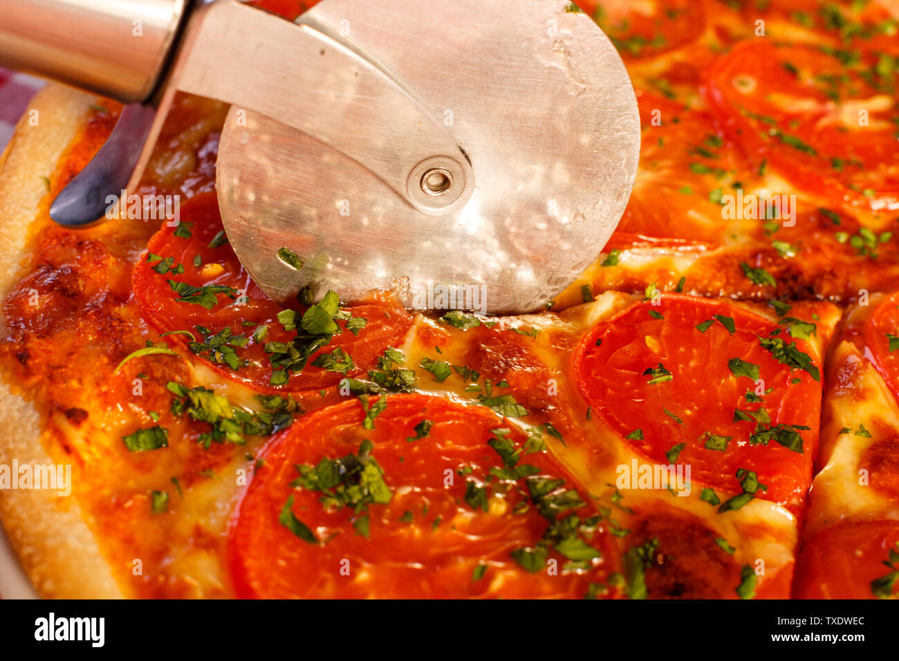 Close up Cuts with a pizza cutter. Pizza Margarita. Delicious hot food sliced and served on white platter. Menu photo, Italian fast food. - Stock Image