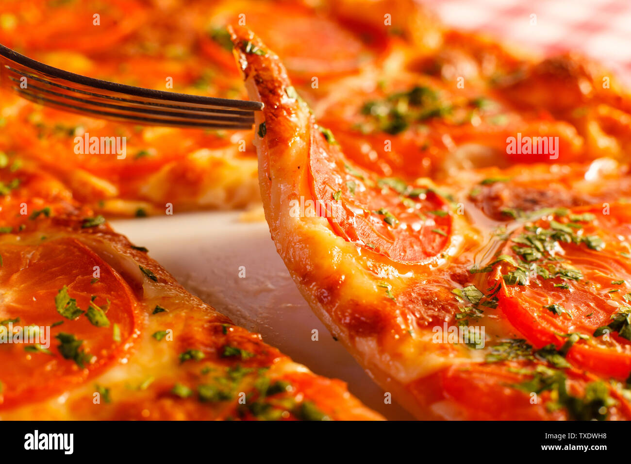 Close up eating piece of pizza with a fork, Pizza Margarita. Delicious hot food sliced and served on white platter. Menu photo, Italian fast food. - Stock Image