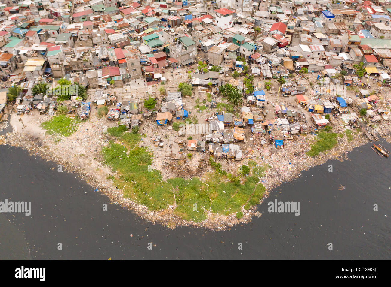 Slums in Manila, a top view. Sea pollution by household waste. Plastic trash on the beach. - Stock Image