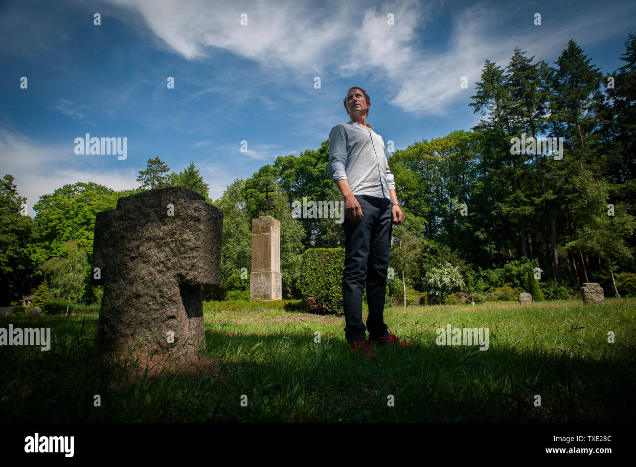 Author and Historian Florian Huber at Demmin Cemetery standing on the Memorial and mass grave site of the mass suicide victims from WW2. - Stock Image