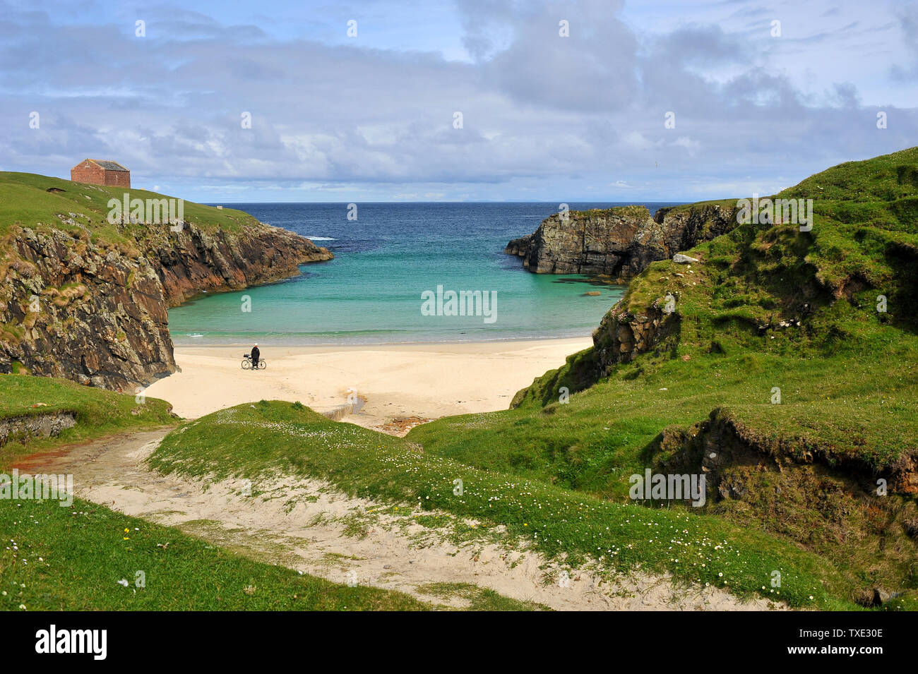 A cyclist enjoys a sunny day on deserted beach in the Outer Hebrides - Stock Image
