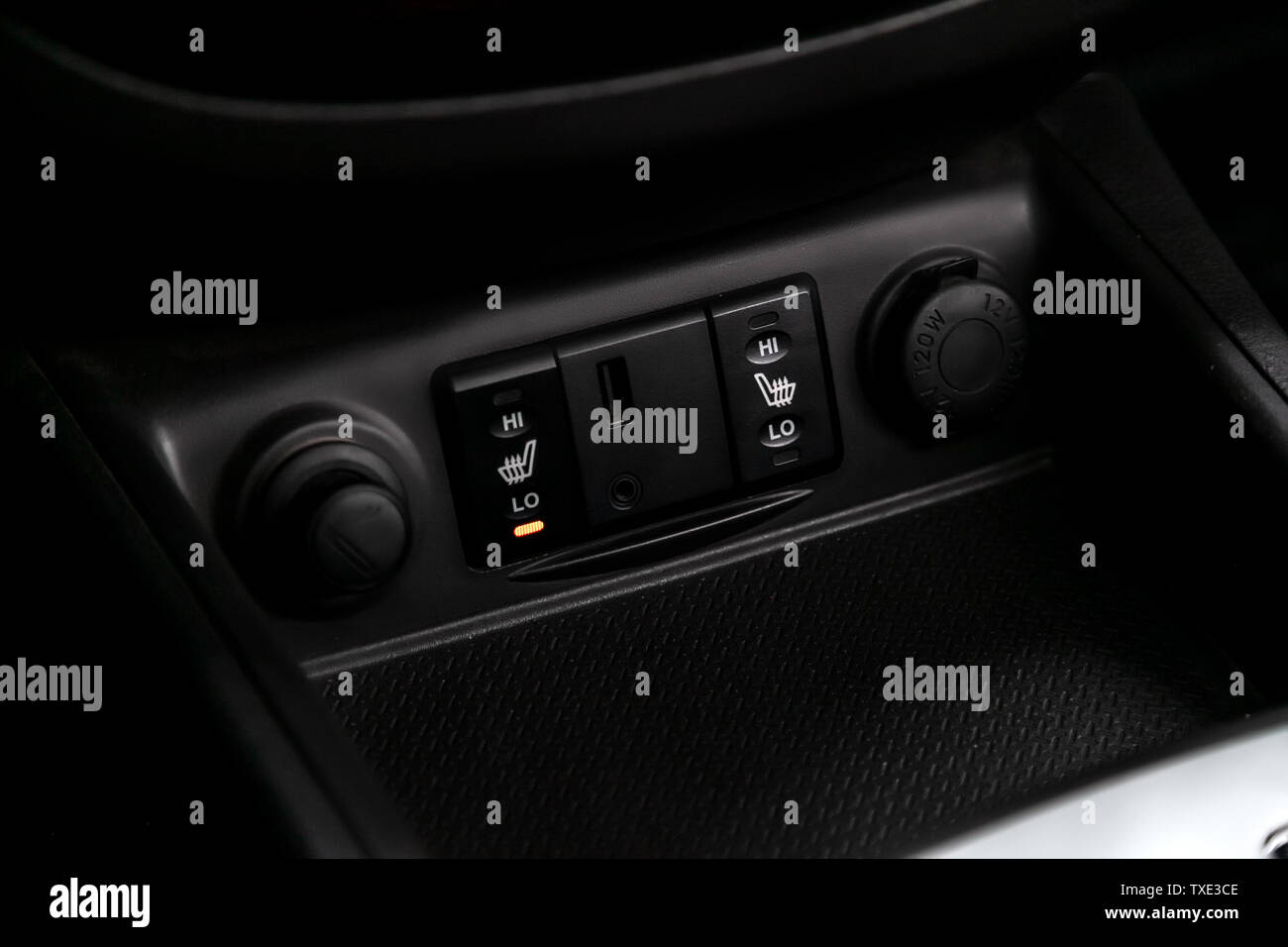 Close-up on the seat heatting buttons. modern car interior: parts, buttons, knobs Stock Photo