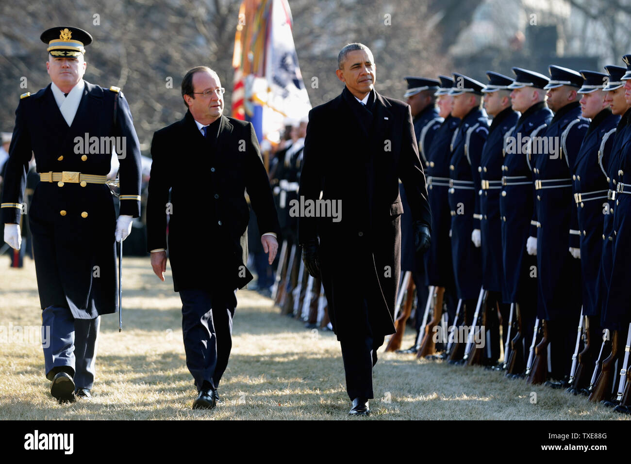 WASHINGTON, DC - FEBRUARY 11:  (AFP OUT)  U.S. President Barack Obama (R) walks with French President Francois Hollande (C) for a military review during a welcoming ceremony on the South Lawn at the White House on February 11, 2014 in Washington, DC. Hollande who arrived yesterday for a three day state visit, visited Thomas Jefferson's Monticello estate and will be the guest of honor for a state dinner tonight.  (Photo by Chip Somodevilla/Getty Images) - Stock Image