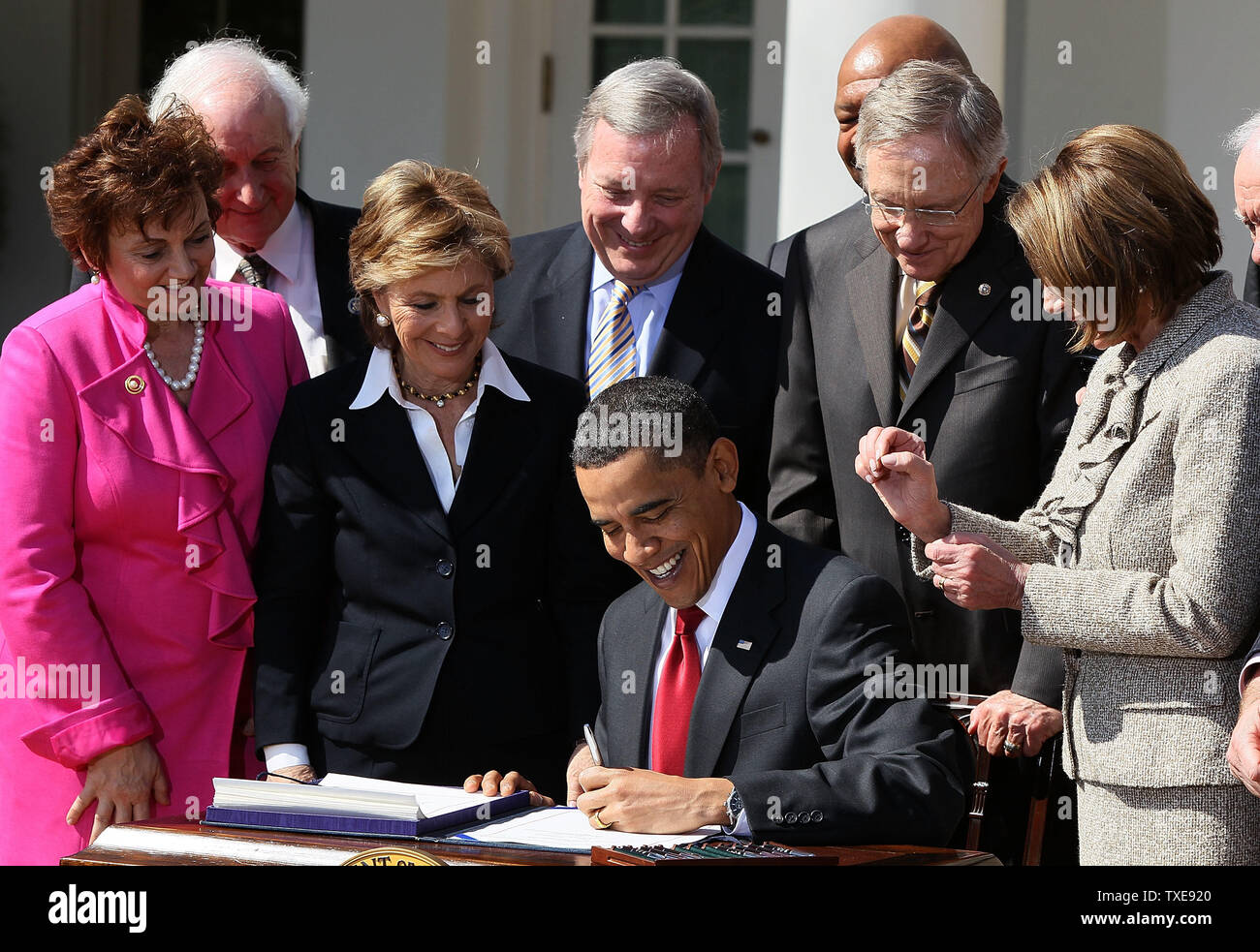 WASHINGTON - MARCH 18: Surrounded by members of Congress, U.S. President Barack Obama signs the Hire Act during a ceremony in the Rose Garden at the White House on March 18, 2010 in Washington, DC. The HIRE Act will offer a payroll tax break for businesses that hire unemployed workers and will offer businesses an income tax credit of $1,000 for retaining these employees.  (Photo by Mark Wilson/Getty Images) - Stock Image