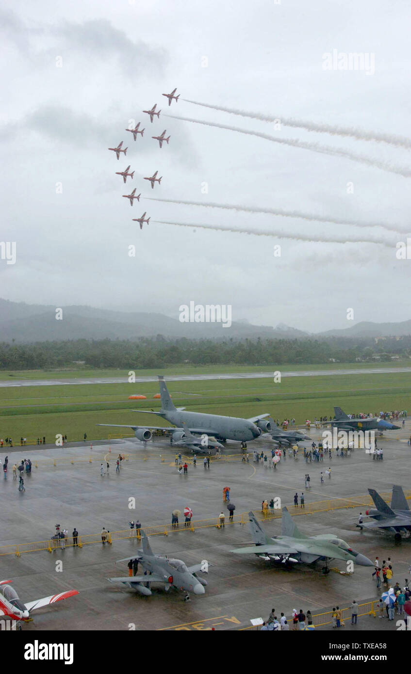 A KC-135 tanker from the 909th Air Refueling Squadron, Kadena Air Base, Japan, and F-16 fighter aircraft from the 35th Fighter Squadron, Misawa Air Base, Japan, is on display on the tarmac while the British Red Arrow demonstration team performs aerial stunts during the Langkawi International Maritime and Aerospace exhibition 2003 (LIMA 03) here. LIMA 03 is one of the premier defense trade show in the world that features over 800 local and international companies and military delegations from about 40 nations that offer state-of-the art aerospace and maritime products.  More than 100 aircraft a - Stock Image