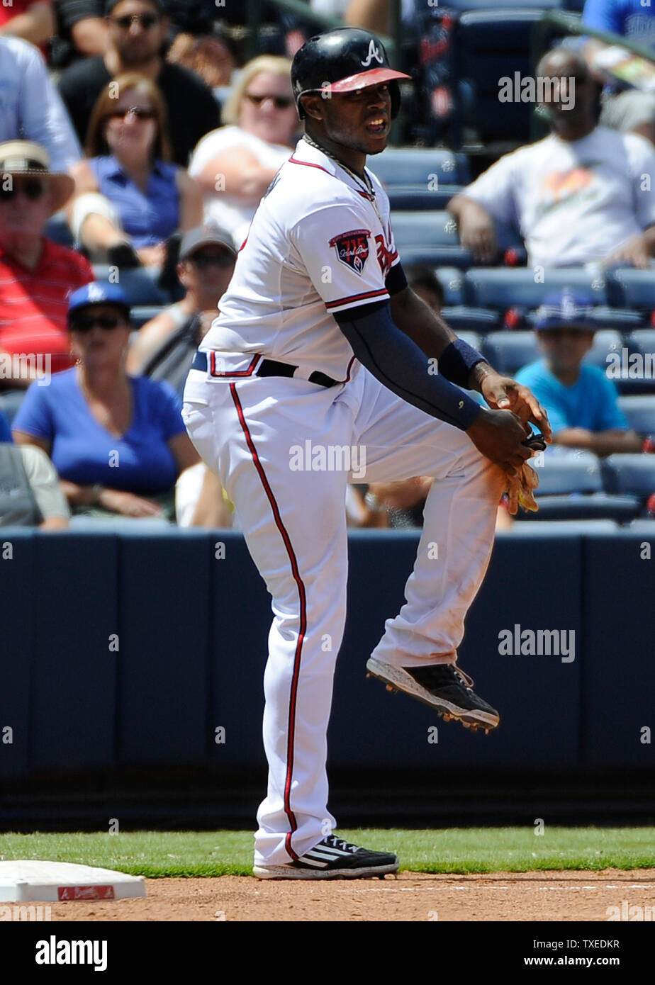 Atlanta Braves left fielder Justin Upton massages his left knee after sliding into third base against the Los Angeles Dodgers before leaving the game with medical personnel in the eighth inning at Turner Field in Atlanta, August 14, 2014. UPI/David Tulis - Stock Image